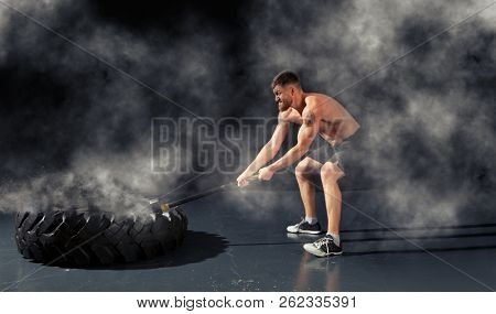 Man hitting wheel tire with hammer sledge. Fitness training