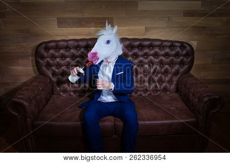 Funny Unicorn In Elegant Suit Sits On Sofa With Bottle Of Wine. Unusual Man With Headache At Home. F