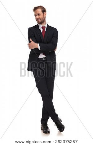 confident businessman stands cross-legged on white background and looks down to side, full length picture