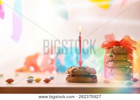 Birthday Candle Lit Over Chocolate Cookies On A Table With Candy And Colorful Ribbons Hanging In Bac