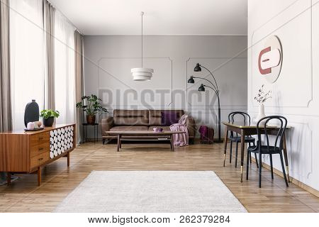 Black Chairs At Table Near Wooden Cabinet In Vintage Living Room Interior With Leather Sofa. Real Ph