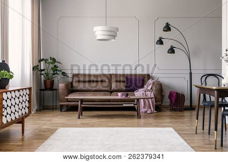 Table In Front Of Leather Couch With Pink Blanket In Flat Interior With Plant And Lamp. Real Photo