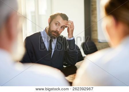 Pensive young man touching his head while looking at one of employers and listening to his words