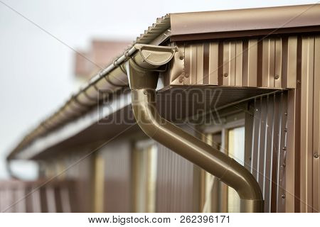 Close-up Detail Of Cottage House Corner With Metal Planks Siding And Roof With Steel Gutter Rain Sys