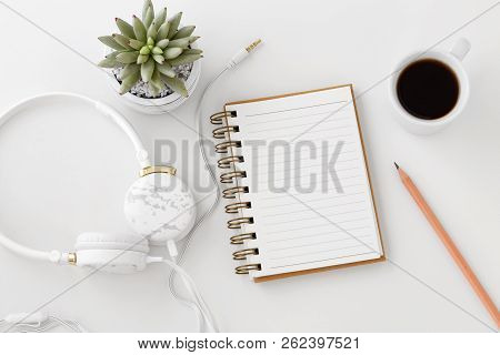 Headphones With Notebook, Pencil, Coffee Cup On White Desk