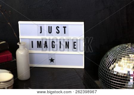 Light Led Box With Typesetters Font Just Imagine Stands On A Leather Table Next To A Vase, Flowers.