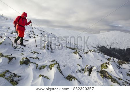 Tourist Hiker In Bright Red Clothing With Walking Sticks Descending Dangerous Rocky Mountain Slope C