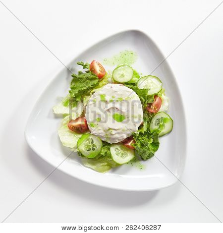 Hummus, Humus or Hommos with Cucumbers, Tomatoes and Lettuce Salad Isolated on White Background. Levantine Dip or Spread made from Chickpeas, Tahini, Olive Oil, Lemon Juice, Salt and Garlic Top View