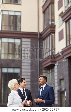 Confident handsome African businessman in suit sharing his creative plan with colleagues while they standing at office building, multi-ethnic business people talking about company