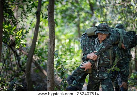 Asian Army Soldier Carries A Wounded Soldier Evacuate At Across The Deep Forest.