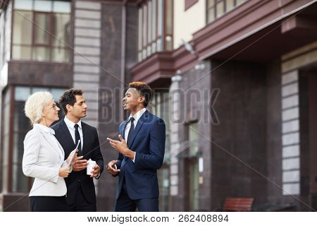 Modern business colleagues discussing project outdoors: confident handsome African-American businessman gesturing hand while explaining his strategy while they walking over financial district