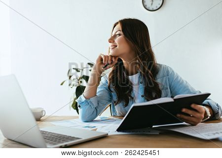 Pensive Businesswoman With Notebook Sitting At Workplace With Papers And Laptop In Office