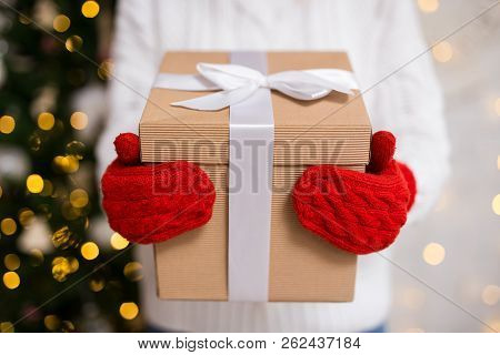 Close Up Of Female Hands In Gloves Holding Gift Box Over Decorated Christmas Tree