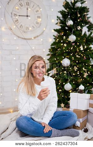 Portrait Of Happy Young Woman Drinking Coffee In Living Room With Decorated Christmas Tree