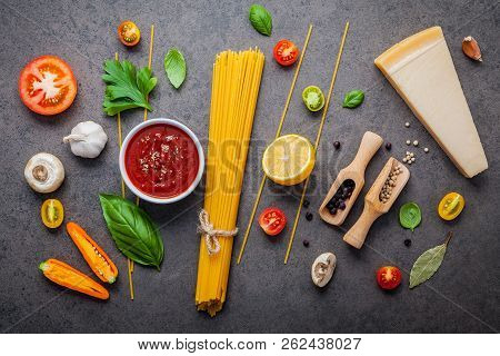 The Thin Spaghetti On Dark Stone Background. Yellow Italian Pasta With Ingredients. Italian Food And