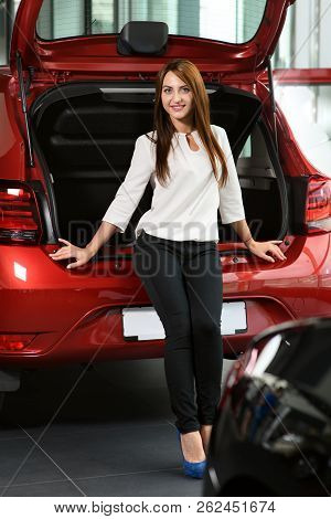 Beautiful Girl Is Sitting On The Car Trunk. She Is Looking For New Car In The Car Dealership. Car Is