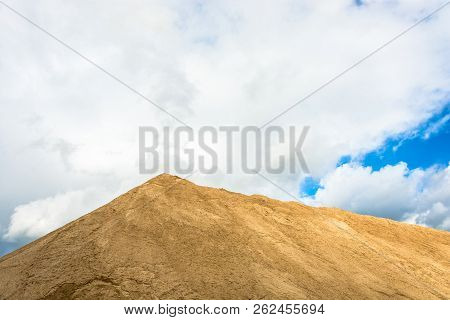 A Large Mountain Of Sand Against A Cloudy Sky.
