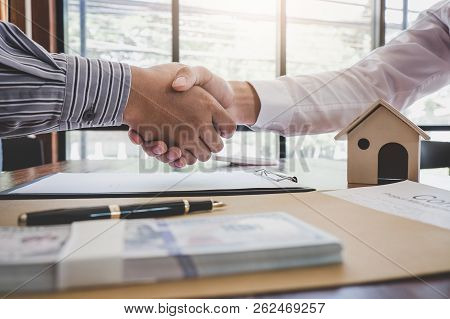 Real Estate Broker Agent And Customer Shaking Hands After Signing Contract Documents For Realty Purc