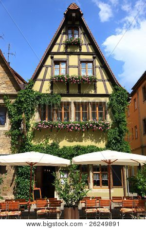 Quaint cafe in Rothenburg, Germany with flowering window boxes poster