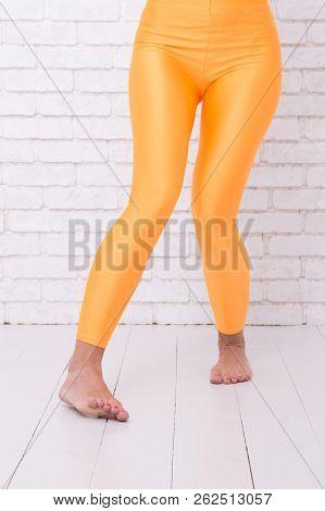 Woman In Orange Leggings On Legs. Sport Wear Fashion. Orange. Practicing In Ballet Studio. Dancing B