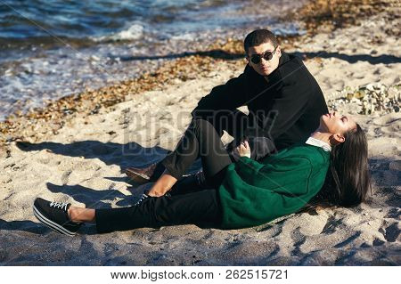 Fashionable Young Couple On The Rocks .young Couple In Love At The Seaside On Autumn Day