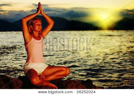 Young woman meditating at sunset time near ocean