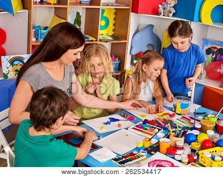 Child dough play in school. Homemade playdough and plasticine for children in kindergarten. Kids knead modeling clay with hands in preschool. Zoo from plasticine. Friendship in children's team.