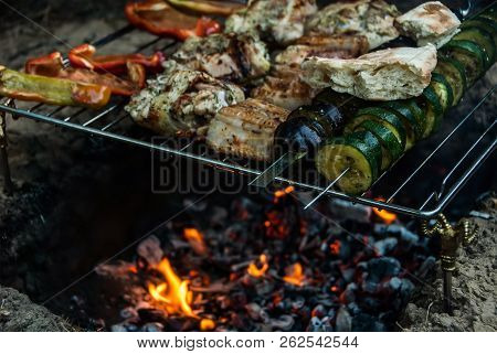 Meat And Vegetable Shish Kabobs Grilling On Fire With Flames. Barbecue In Tourist Forest Camp. Conce