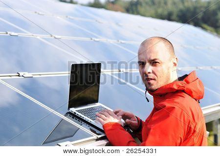 Männlich-Ingenieur mit Laptop, Sonnenkollektoren im Hintergrund