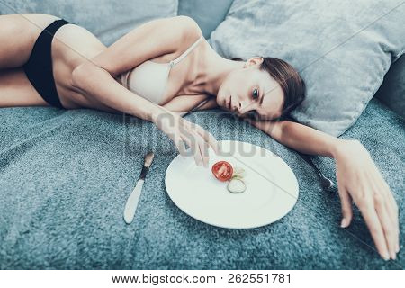 Slim Girl With Anorexia Lying On Sofa With Plate. Sliced Vegetables. Woman With Anorexia. Weigth Pro