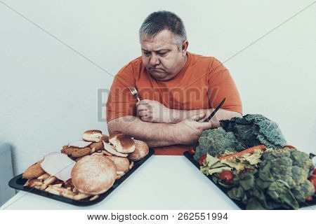 Fat Upset Man With Trays With Food On White Table. Man With Bulimia. Unhealthy Lifestyle Concept. Si