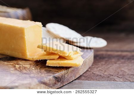Block Of Cheddar Cheese And Slices Over A Rustic Background.. Extreme Shallow Depth Of Field With Se