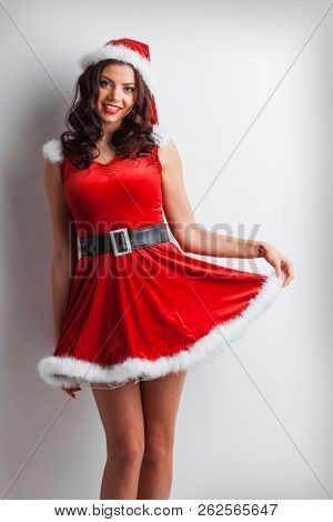 Pretty Pin-up style Santa girl in red hat and dress on white background
