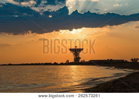 Magnificent Sunset On The Background Of The Sea And Space Antenna. The Rays Of The Sunset Illuminate