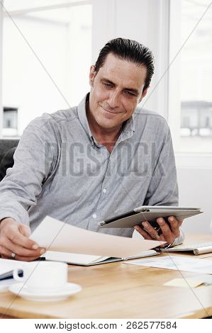 Mature Manager Reading Document While Sitting At The Table And Working Online On Touchpad