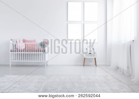 Mockup Of Empty Posters Above Cabinet In White Kid's Room Interior With Cradle And Carpet. Real Phot