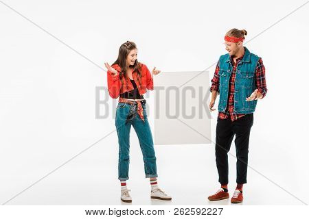 Stylish Hipster Couple Holding Empty Banner And Doing Shrug Gesture Isolated On White