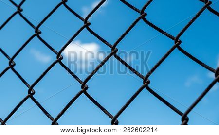 Selective Focus On Chain Link Fence With Blue Sky And Clouds In The Background