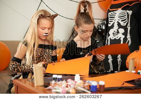 Concentrated Pretty Little Girlfriends In Beautiful Halloween Dresses Cutting Out Colored Paper Whil