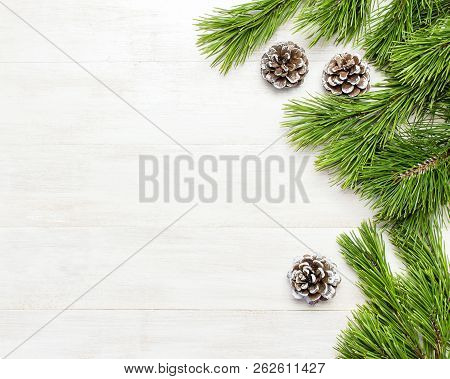 Christmas Background, Green Pine Branches, Cones Decorated With Snow On White Wooden Table. Creative