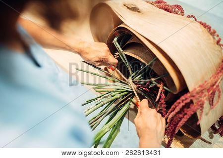 Female florist ties a bouquet of flowers in shop