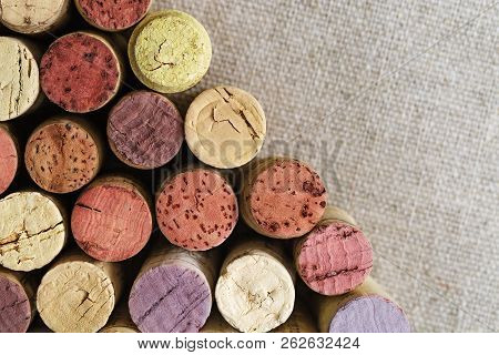 Close Up Of Wine Corks On Blurred Sackcloth With Copy Space. Wine Corks Arranged In Left Corner Hori