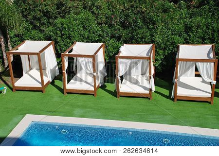 Four poster sunbeds by a swimming pool at Puerto Pollensa on the Spanish island of Majorca.