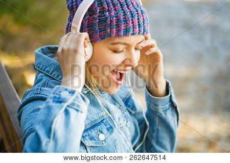 Girl Listens To Music In Headphones. Smiling Girl Relaxing, Music A Smartphone And Headphones. Outdo
