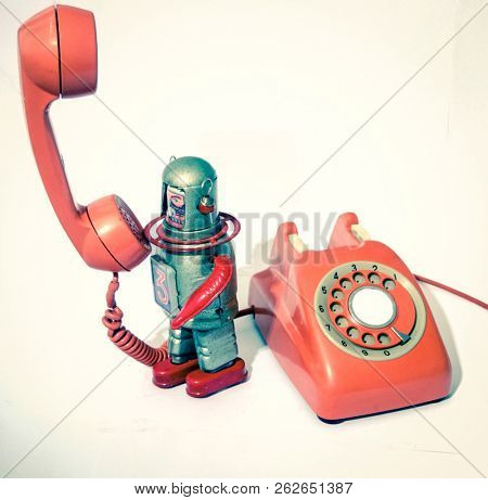retro robot on an old phone robot calls  toned image