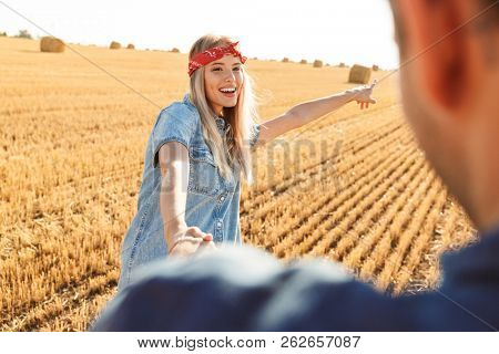 Picture of amazing young cute loving couple standing on the field walking outoors pointing.