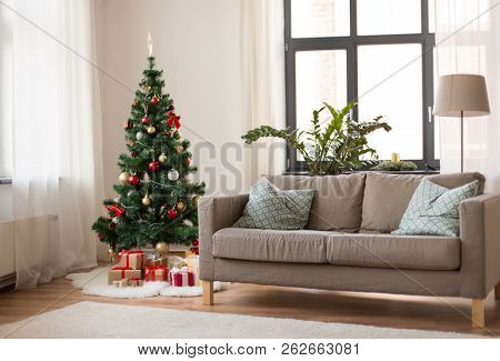 winter holidays and interior concept - christmas tree, gifts and sofa at cozy home living room