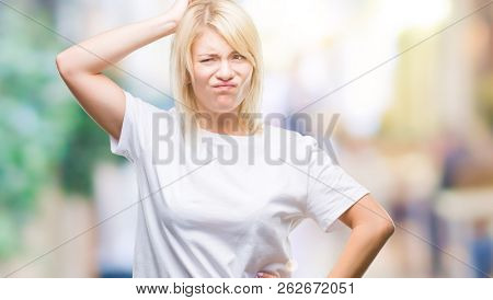 Young beautiful blonde woman wearing white t-shirt over isolated background confuse and wonder about question. Uncertain with doubt, thinking with hand on head. Pensive concept.