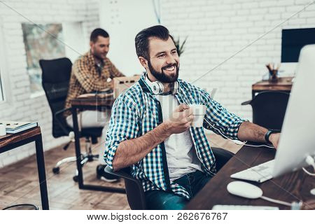 Smiling Bearded Man Sitting On Chair In Office. Didital Device On Desk. Modern Office, Black Chair.