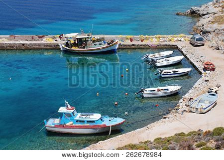 TILOS, GREECE - JUNE 13, 2017: Small boats moored at Livadia harbour on the Greek island of Tilos. The Dodecanese island has a population of around 780 people.